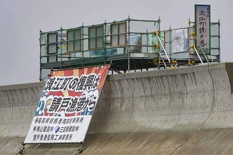 Namiessa aallonmurtajan kyljessä on juliste. Siinä kerrotaan kaupungin jälleenrakentamisen alkavan satamasta.