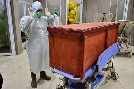 Sairaalan työntekijä rukoilee koronavirustautiin menehtyneen potilaan arkun äärellä Indonesiassa 9. syyskuuta.