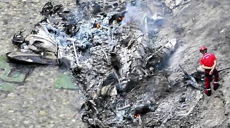 Pelastusviranomainen tarkasteli pudonneen helikopterin savuavia jäänteitä.