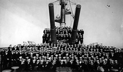 Panssarilaiva Ilmarisen miehistö järjestäytynyt keulakannelle kuvaukseen 10-tuumaisten tykkien alle vuoden 1936 kertausharjoitusten yhteydessä.