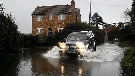 Autoilijat halkovat tulvavettä tiellä Stathessa.