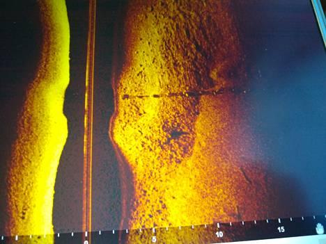 Esimerkkikuva viistokaikuluotaimen tuottamasta kuvasta. Kuva ei liity Jussi Peltolan tapaukseen. Kuvassa näkyy pohjaan painotettu vesijohto kivikkoisella pohjalla.