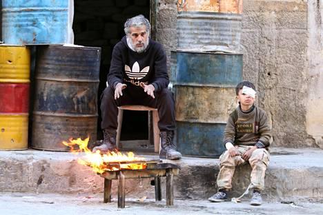 Mies ja poika lämmittelivät avotulen ääressä perjantaina. Saarretussa Itä-Aleppossa asukkaita uhkaavat myös kylmyys ja ruoan loppuminen.