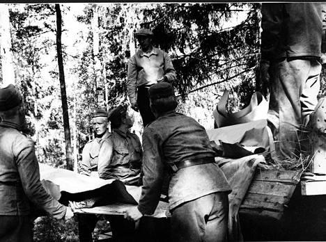 Järkyttyneitä sotilaita kantamassa tyttöjen ruumiita lavetilla kuorma-autoon.