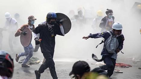 Mielenosoittajat pakenivat kyynelkaasua Yangonin kaduilla tiistaina.