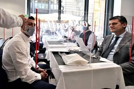 Ravintolakuumetta? Tarjoilija mittasi asiakkaan lämmön Milanossa, Italiassa, kun ravintolat saivat avata ovensa tiukkojen koronaturvatoimien kera.