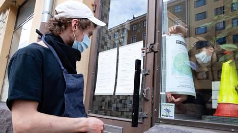 Ravintoloitsija Ossi Paloneva seurasi ulkona, kun suunnittelija Erwin Laiho asetteli ikkunaan ilmoitusta ravintolan kotiinkuljetusalueesta maaliskuussa.