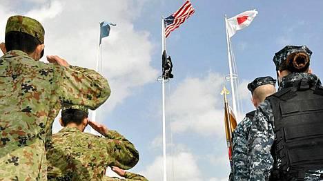 Japanilaiset ja amerikkalaiset tervehtivät lippuja sotaharjoitusten aluksi.