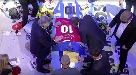 Argentiinan presidentti Alberto Fernandez (vas.) asetti Argentinos Juniors -joukkueen paidan Maradonan arkulle. Seuran johtaja Cristian Malaspina kumartui suutelemaan arkkua.