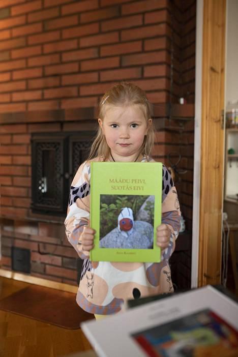 Frida esittelee saamenkielistä kirjaansa. Äiti Varpu Falk kertoo, että kirjallisuutta ilmestyy hitaasti lisää, kiitos Saamelaiskäräjien ja Inarinsaamen kielen yhdistyksen. –Saamen radiossa kuuluu ja näkyy kaikki kolme saamenkieltä, Falck kiittelee.
