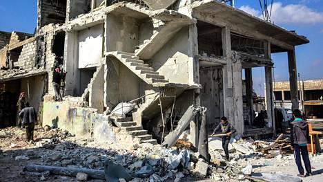 Paikalliset tutkivat ilmaiskuissa vaurioitunutta rakennusta Idlibin kaupungissa Syyriassa 29. tammikuuta.
