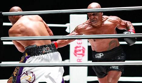 Tyson (oik.) jakeli ottelussa painavia iskuja Jones Juniorin keskivartaloon.