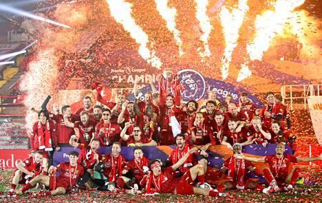 Liverpoolin kapteeni Jordan Henderson nostamassa mestaruuspokaalia joukkuetovereiden ja seuran työntekijöiden ympäröimänä keskiviikkoisen Chelsea-pelin jälkeen.