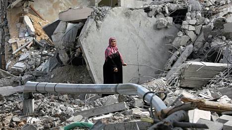 Palestiinalaisnainen tutki talonsa raunioita.
