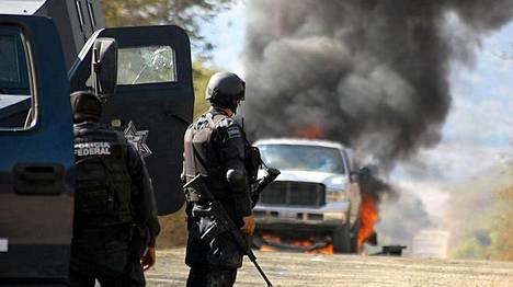 Poliisit katsoivat palamaan ammuttua huumekartellin pyssymiesten autoa La Familia -kartellin sydänalueella Apatzingassa torstaina.