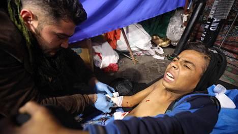 Haavoittunutta mielenosoittajaa hoidetaan perjantaina Irakin pääkaupungissa Bagdadissa.