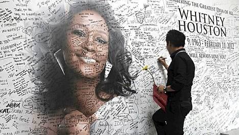 Filippiiniläinen fani kirjoittaa muistosanoja Whitneylle seinään.