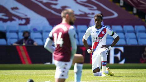Crystal Palacen Wilfried Zaha (oik.) polvistui ennen ottelua Aston Villaa vastaan sunnuntaina.