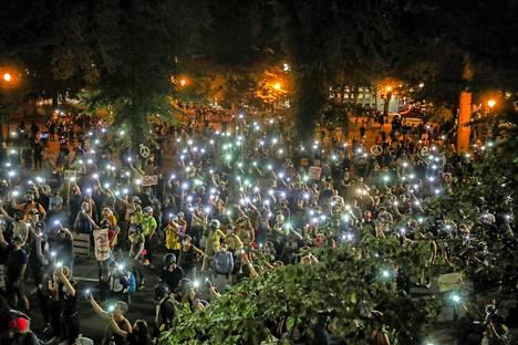 Mielenosoittajien ylös nostamat valaistut puhelimet loistivat illassa.