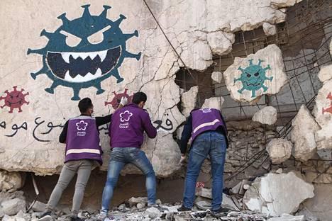 Vapaaehtoisjärjestön edustajat maalasivat rauniotalojen seiniin varoituksia koronaviruksesta Idlibin maakunnassa torstaina.
