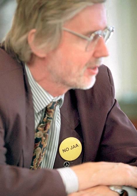 """EU-kriitikoiden infossa 12.10.1994 Erkki Tuomiojan rinnassa on perinteisen rauhanmerkin päällä keltainen nappi, jossa lukee """"NO JAA"""". Näitä merkkejä teetettiin Rauhanasemalla vain muutama kappale Tuomiojan omaan käyttöön."""