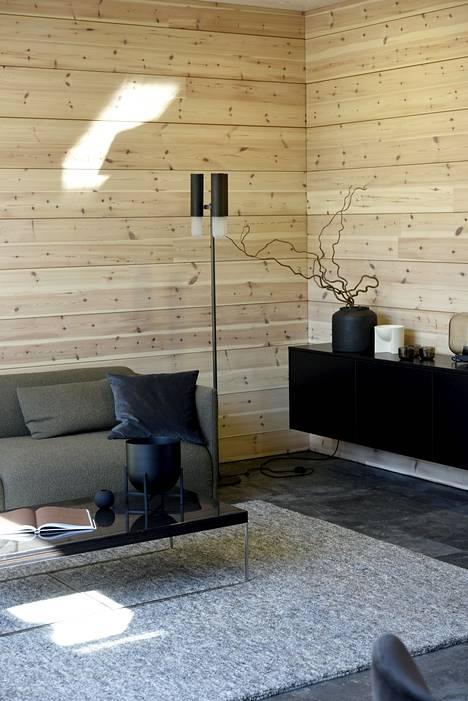 Kontio-talossa on haettu modernia linjakkuutta. Talon suunnittelussa on inspiroiduttu tumman ruskean sävyistä. Sisustuksen pääsuunnittelijana on ollut Piia Kalliomäki. Sohva Adea, sohvapöytä Skanno, matto Woodnotes, jalkavalaisin Skanno, tv-taso Kontio Living.