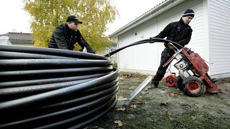 Maalämpöpumpulle kairataan 200 metriä syviä reikiä rivitalon pihalla Lohjalla vuonna 2009. Kuvassa Anton Puhakka ja John Ojanen asentavat maalämpöputkia kairattuihin reikiin.