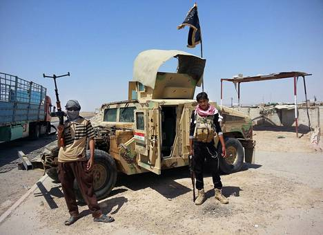 Isis-taistelijat poseeraavat haltuunsa saaman Humveen vieressä.