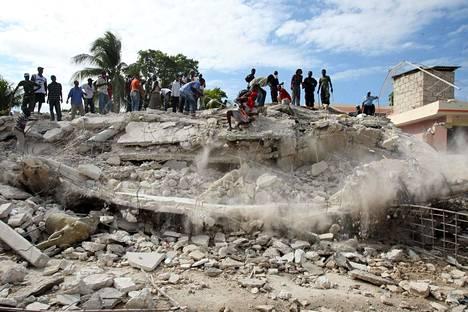 Ihmisiä tutkimassa rakennuksen raunioita kaksi päivää maanjäristyksen jälkeen tammikuussa 2010.
