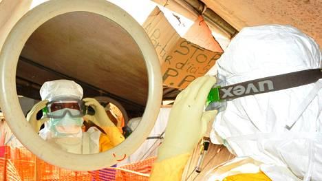 Hoitaja asettelee suojavälineitä ylleen ebolaklinikalla Guineassa.