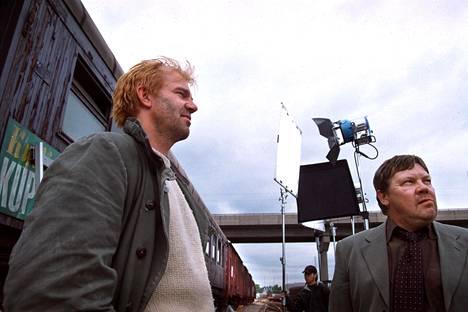 Pornokauppias Sundmanin rooli Raidissa on yksi Mujeen tunnetuimpia. Kuvassa Kai Lehtinen (vas) ja Juha Muje kuvaustauolla 2002.