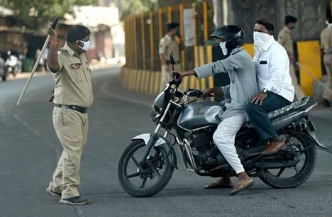 Poliisi heiluttaa pamppua miehelle, joka rikkoo ulkonaliikkumiskieltoa.