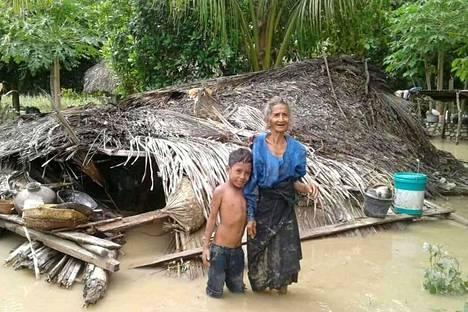 Nainen kahlasi lapsenlapsensa kanssa vedessä Haitimukin kylässä.