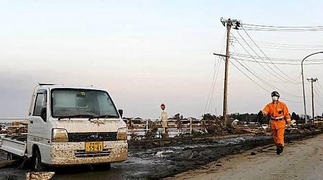 Pelastustyöntekijä käveli tuhoutuneessa Sendain kaupungissa.