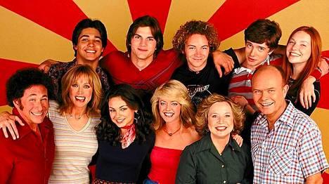 Koko 70's Show -näyttelijäkaartin ryhmäkuvassa Ashton ja Danny poseerasivat takarivissä toisena ja kolmantena vasemmalta.