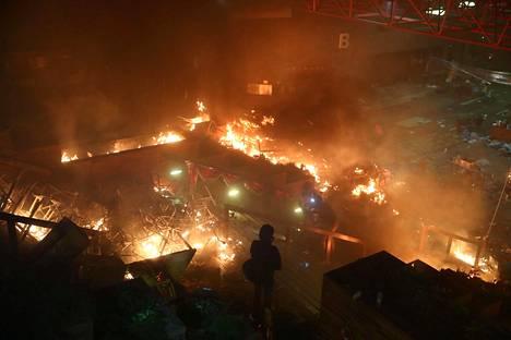 Mielenosoittaja katsoo tulipaloa Hongkongin polyteknisellä yliopistolla 18. marraskuuta 2019.