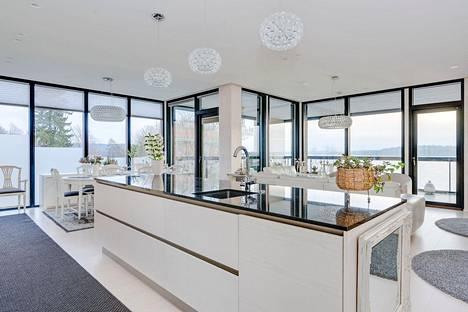 Asunnon keittiöstä pääsee nauttimaan upeista näkymistä Pyhäjärvelle lattiasta kattoon ulottuvien ikkunoiden läpi.