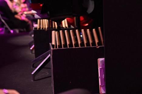 Pistekyltit on sijoitettu puiseen laatikkoon tuomaripöydän alle.