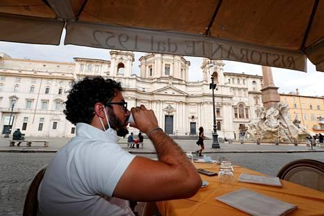 Mies siemaili espressoa Rooman Piazza Navonalla sijaitsevassa ravintolassa maanantaina.