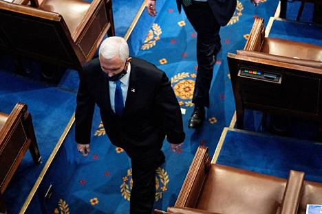 Silloinen varapresidentti Mike Pence kävelemässä pois edustajainhuoneen salista kesken tulosten varmistamisen, kun väkijoukko oli tunkeutunut kongressirakennukseen.