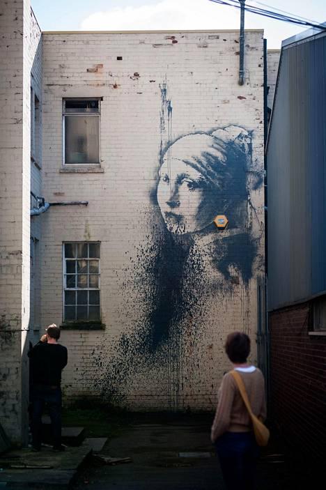 Banksyn Bristolissa vuonna 2014 maalaama Tyttö ja helmikorvakoru.