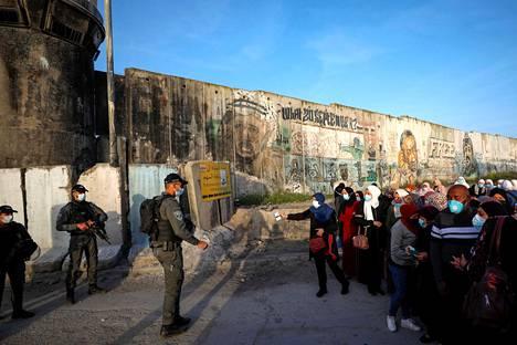 Palestiinalaiset esittivät henkilöpapereitaan israelilaiselle rajavartijalle Länsirannan Israelista erottavalla muurilla Ramallahissa. Väkijoukko oli pyrkimässä rukoilemaan Al-Aqsalle ramadanin ensimmäisenä perjantaina.