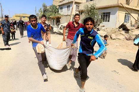 Mosulilaismiehet kantoivat haavoittunutta poikaa pois taisteluista lauantaina.