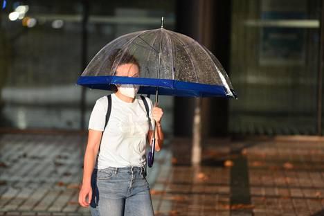 Nuori nainen suojasi itseään ja maskiaan sateelta syyskuussa Barcelonassa Espanjassa.