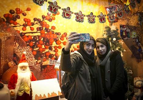 Iranilaiset naiset ottivat selfieitä joulukoristeiden edessä Teheranissa ennen joulua. Etenkin nuoret naiset sitovat nykyisin huivit löysemmin päähän kuin aiemmin.