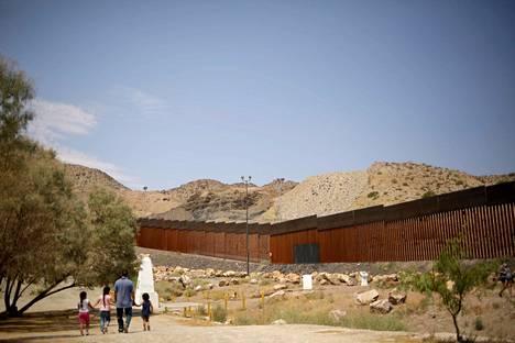 Perhe käveli muurinosan ohi, joka rakennettiin Trump-kannattajien lahjoitusrahoilla.