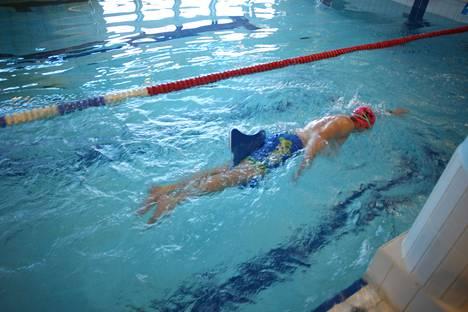 Petri Savinainen harjoittelee vapaauintia uimalauta jalkojen välissä. Lauta auttaa jalkojen asennon hallinnassa ja antaa sen verran vastusta, että vartalonkierron tuntee hyvin.