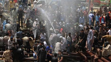 Asukkaat vilvoittelevat vesipostien suihkeessa Karachissa.