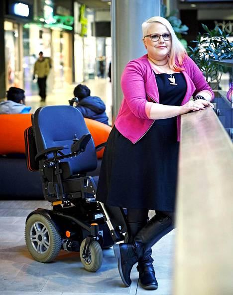 Riikka Nieminen käyttää sähköpyörätuolia, mutta voi myös nousta siitä tarpeen tullen. – Kun olen sähköpyörätuolissa, ihmiset lähestyvät varovaisemmin kuin rollaattoria käyttäessäni.