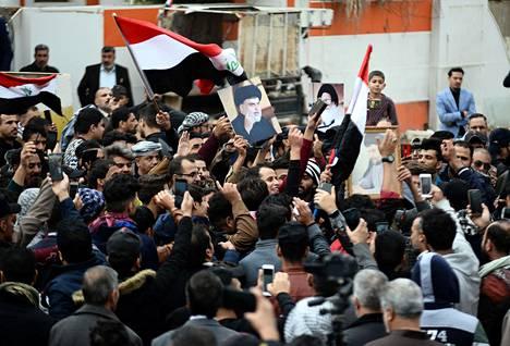 Moqtada Sadrin kannattajat pitelevät shiiajohtajan kuvaa hänen kotinsa lähellä järjestetyssä mielenosoituksessa lauantaina.